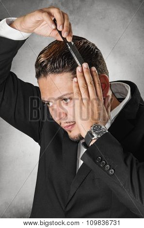 Elegant man in dark suit combing his hair