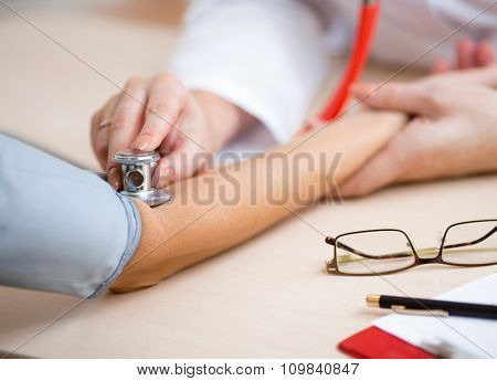 Doctor measuring blood pressure at desk