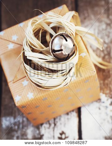 Christmas Box with Jingle Hand Bell and Natural Twine on Wooden Background. Toned image poster