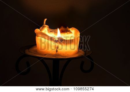 White Candle With Flame And Melting Wax On An Iron Candlestick Against A Dark Background