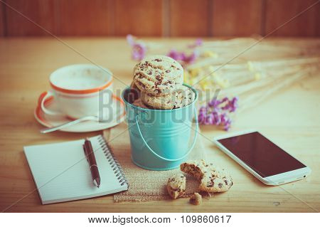 Chocolate chip cookies in black ceramic dish with smartphone notebook and pen and coffee cup at cafe in morning time with vintage filter effect