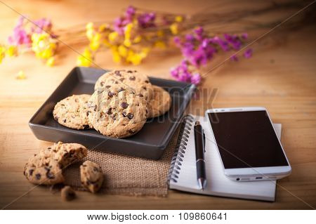 Chocolate chip cookies in black ceramic dish with smartphone notebook and pen and coffee cup at cafe in morning time