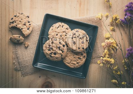 Chocolate chip cookies in black ceramic dish at cafe in morning time with vintage filter effect