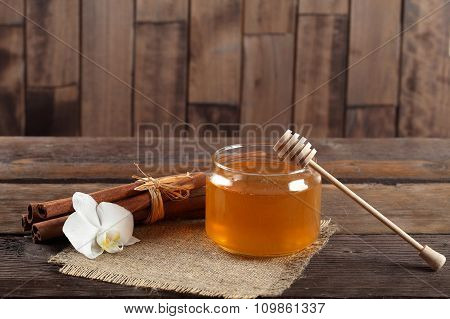 Heather honey and cinnamon on wooden table.