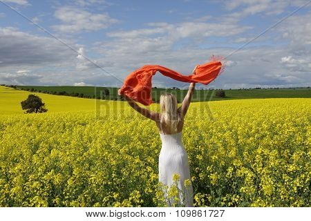 Happy Woman Flailing Scarf In A Field Of Flowering Canola In Spring