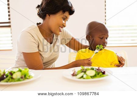 pretty african mother trying to feed her little son who hates eating green salad