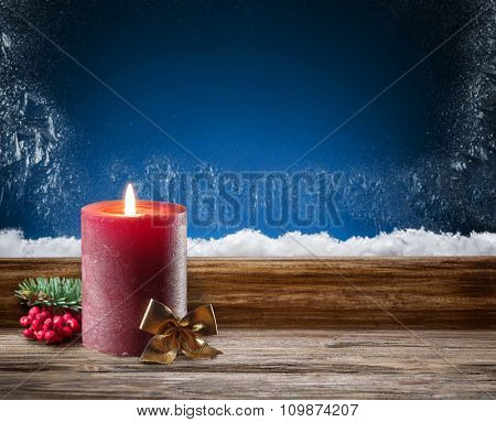 Winter window with burning candle. In the night.