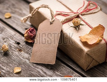 Gift tag with gift box on a vintage wooden background. Close-up shot.