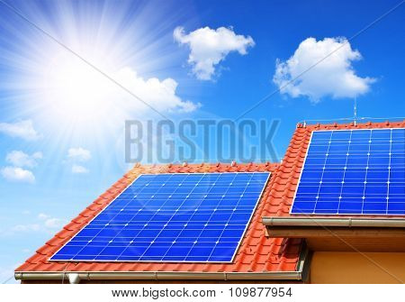 Solar panel on the roof of the house in the background sunny sky.
