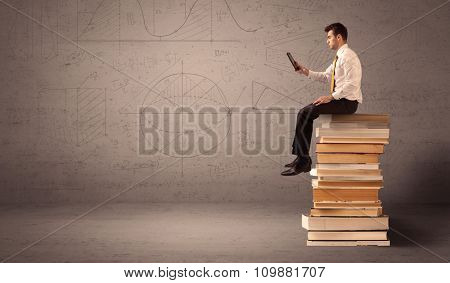 A serious businessman with tablet in hand in suit sitting on a pile of giant books in front of a greyish brown wall including drawn lines, angles, numbers, circles and curves.