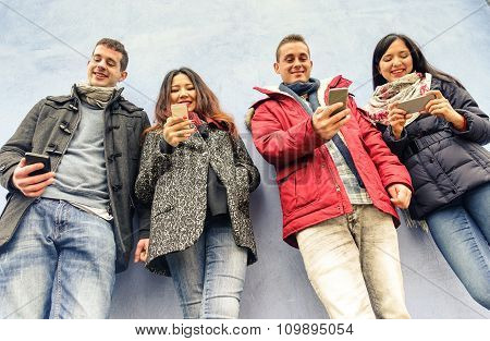 Group Of Young Friends Looking Their Smartphones In Oldtown Centre