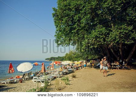 Sunny Beach With Relaxed People, Umbrellas And Big Green Trees Of Turkish National Park