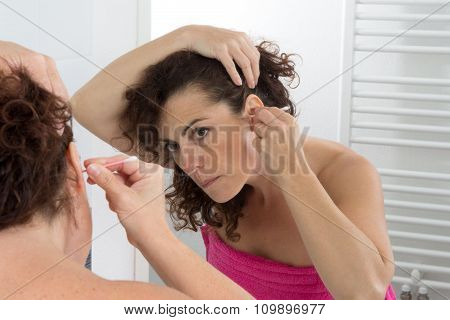 A Curly Brunette Woman Cleans Her Ear At Home