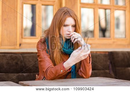 Embarrassed sad shoked young redhead lady reading message in mobile phone sitting in open air cafe