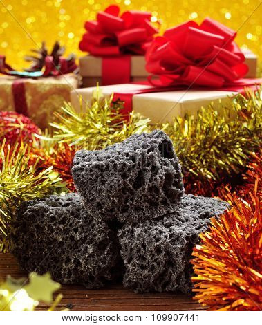 closeup of some lumps of candy coal and some christmas ornaments and gifts