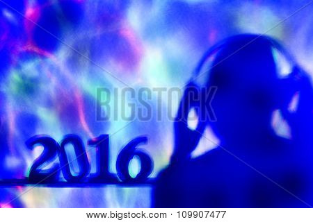 colorful lights projected on the number 2016, as the new year, and a disc jockey man wearing headphones in a dance club