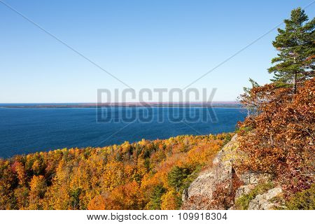 Blue Lake, Autumn Leaves, And A Clear Blue Sky