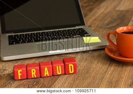 Fraud written on a wooden cube in a office desk