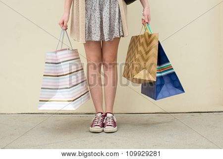 Woman standing holding several shopping bags