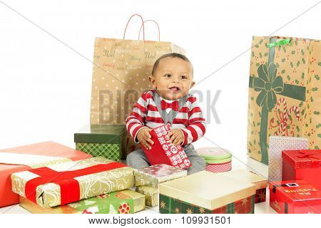 An adorable, dressed up baby boy obviously loving being surrounded by lots of wrapped gifts.  On a white background.