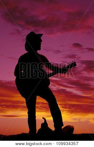 Silhouette Of A Cowboy Foot On Saddle Playing Guitar