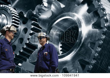 industry woirkers with giant cogwheels and gears machinery, steel and metal industry