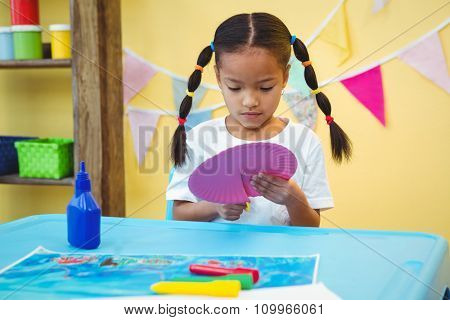 Focused girl cutting a paper plate with scissors