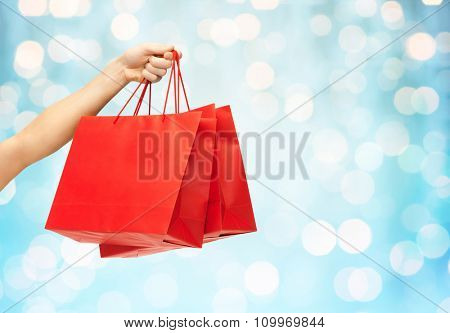 people, sale, consumerism, advertisement and commerce concept - close up of hand holding red blank shopping bags over blue holidays lights background