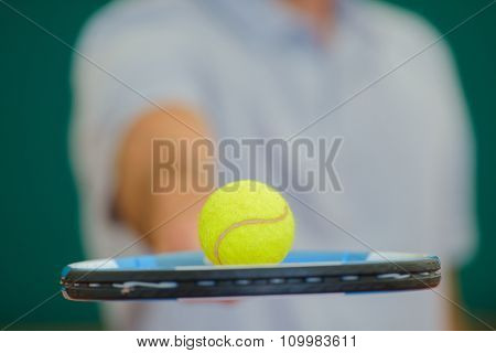 Closeup of tennis ball balancing on racket