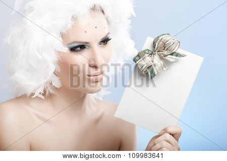 Impish winter beauty in white feather cap and luxurious makeup holding fancy christmas present.
