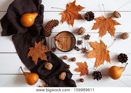 Autumn composition with hot cup coffee cinnamon, scarf, nuts and leaves. Concept of cozy morning, co