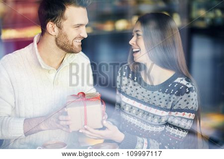Amorous guy and girl congratulating one another on Saint Valentine Day in cafe