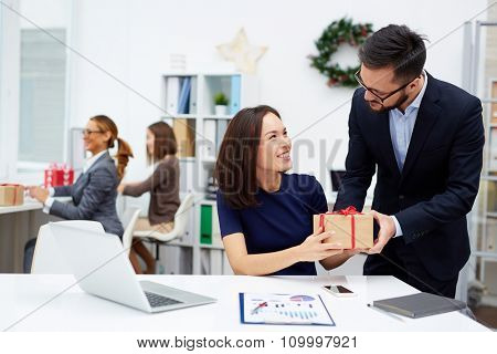 Young businessman giving his colleague Christmas present in office