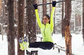Fit girl training abs by raising legs on a horisontal bar. Fitness woman workout doing exercises outdoor winter park poster