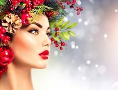 Christmas fashion model woman. Xmas New Year hairstyle and make up. Beauty Girl portrait. Gorgeous Vogue style Lady with Christmas decorations on her head, baubles, professional makeup, red lipstick poster