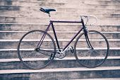 Road bicycle fixed gear bike on city concrete street. Urban industrial cycling bike on city stairs steps bicycle closeup vintage old retro bike cycling or ecology commuting. Industrial concept. poster