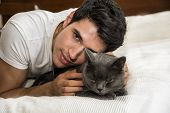 Handsome Young Animal-Lover Man on a Bed, Hugging and Cuddling his Gray Domestic Cat Pet. poster