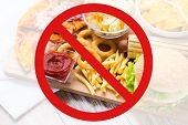 fast food, low carb diet, fattening and unhealthy eating concept - close up of deep-fried squid rings, french fries and other snacks behind no symbol or circle-backslash prohibition sign poster