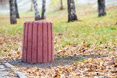 New red cement trash bin in the park in autumn poster