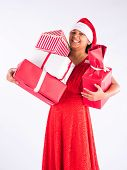 indian girl standing and holding christmas gifts, celebrating christmas with red gown and santa cap, isolated on white background, indian girl, indian teenager, asian girl and christmas, balancing poster