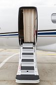 white private jet and open ladder at the airport on concrete Peron poster