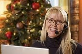 Happy Woman with Phone Headset In Front of Christmas Tree and Computer Screen. poster
