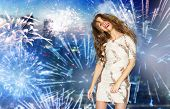 people, style, holidays, hairstyle and fashion concept - happy young woman or teen girl in fancy dress with sequins and long wavy hair dancing at party over firework at night city background poster