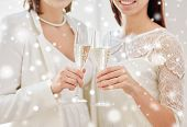 people, homosexuality, same-sex marriage, celebration and love concept - close up of happy married lesbian couple holding and clinking champagne glasses over snow effect poster