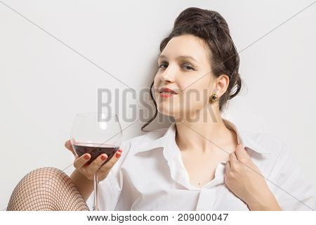 happy woman with red wine on white background sitting, looking at camera
