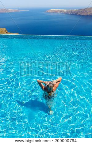 Woman enjoying relaxation in pool and looking at the view in Santorini Greece