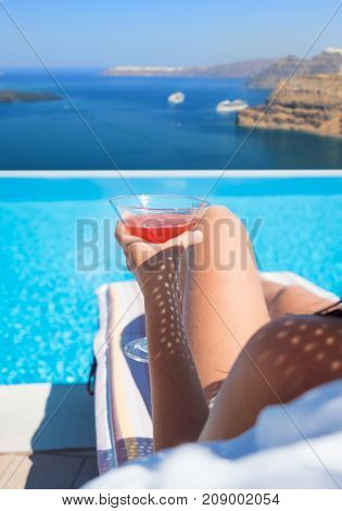 Woman relaxing in infinity swimming pool looking at view in Santorini Greece