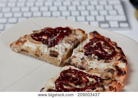 Fresh and tasty pizza near white computer keyboard