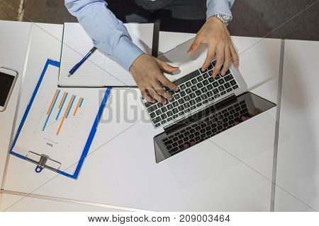 Aerial view of young businessman working on laptop