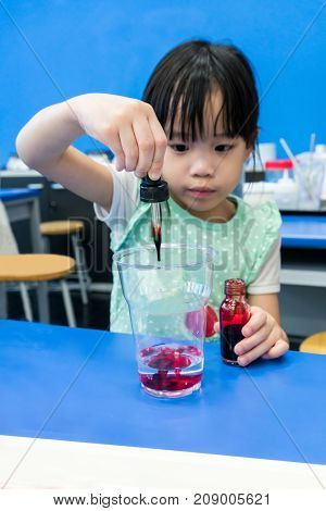 Kindergarten Girl Using Droplet To Add Red Color Into A Cup On Blue Table.